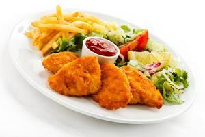 Bocconcini di pollo fritto, patatine fritte e verdure foto