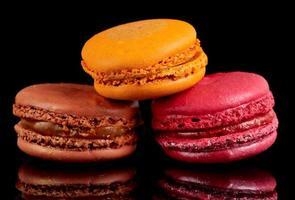 tre macarons colorati su sfondo nero foto