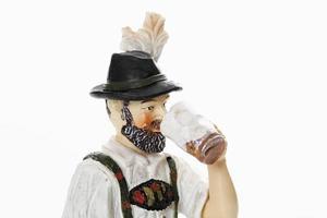 Statuetta bavarese che beve birra da boccale di birra foto