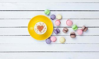 cappuccino con simbolo a forma di cuore e macaron foto