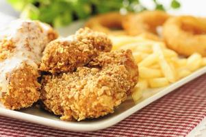 ali di pollo con patatine fritte e anelli di cipolla