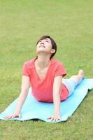donna giapponese che fa posa del cobra di yoga foto