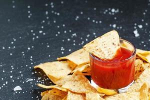 Nachos di mais snack messicani con salsa di pomodoro e sale foto