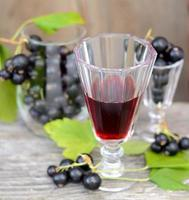 liquore di ribes nero e bacche mature sul tavolo di legno foto
