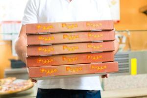 servizio di consegna - uomo che tiene scatole per pizza foto