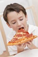 bambino ragazzo che mangia la fetta di pizza foto