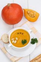 zuppa di zucca con baguette in tazza foto