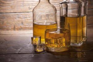 bicchiere di whisky con ghiaccio su uno sfondo di legno