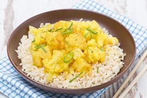 Alimento tailandese - curry di verdure con cavolfiore e riso, primo piano foto