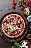 Pizza italiana con salame, funghi e olive sul tavolo di legno foto
