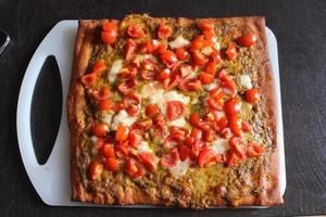 pizza italiana fatta in casa con pesto e pomodori. foto