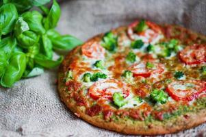 primo piano di pizza vegetariana fatta in casa su fondo di legno foto