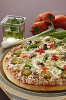 deliziosa pizza con verdure che la circondano nella cornice.