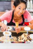 lavoratrice sorridente nella gelateria che tiene un cono foto