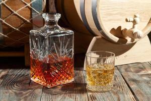 bicchiere di whisky con ghiaccio e decanter