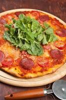 pizza a fette di peperoni, prosciutto e funghi foto