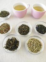 varietà di tè verde e due tazze di tè