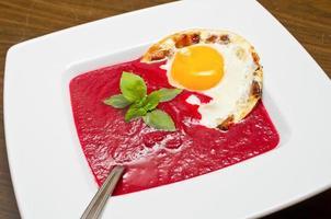 Crema di barbabietole con uovo fritto e pancetta foto