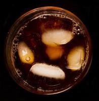 bicchiere con liquido scuro pieno di ghiaccio foto