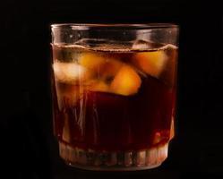 bicchiere con liquido scuro pieno di cubetti di ghiaccio foto