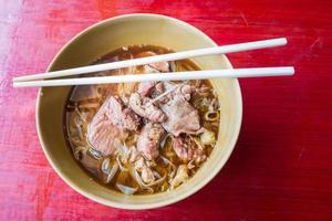 tagliatella asiatica con carne di maiale in umido nella ciotola foto