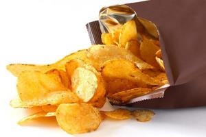 pacchetto aperto di patatine su bianco