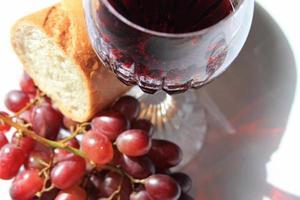 primo piano vino rosso, pane e uva foto