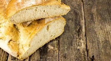 taglio del pane sul tavolo di legno foto