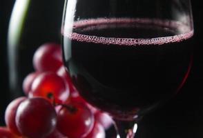uva e bicchiere con vino rosso