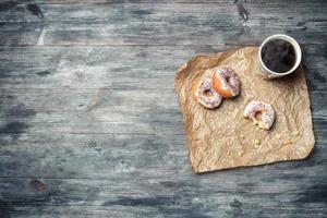 ciambelle e caffè su un tavolo di legno foto