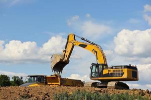 l'escavatore carica il camion con terra foto