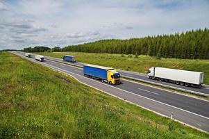 camion che viaggiano su un'autostrada asfaltata tra prati fioriti foto