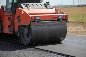 grande rullo rotante che pavimenta una strada. costruzione della strada foto