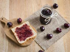 marmellata di ciliegie e toast su fondo in legno