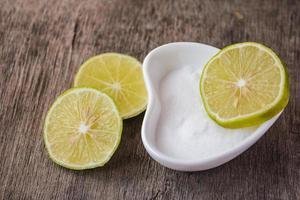 fette di limone sulla ciotola di sale e sul tavolo di legno