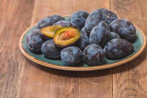 prugne fresche su un piatto foto