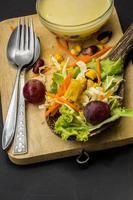 insalata di mais cucchiaio da tavola nero sul pavimento. foto