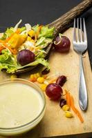 insalata di mais sul cucchiaio da tavola nero sul pavimento. foto