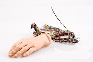mano androide con fili che escono su sfondo isolato foto