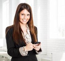 donna che per mezzo di un telefono cellulare foto