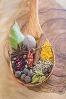cucchiaio di legno con assortimento di spezie foto