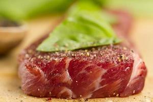 carne di maiale cruda sul tagliere con spezie foto