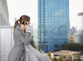 donna di affari che per mezzo del telefono cellulare sul balcone foto