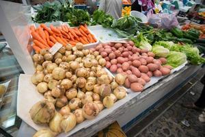 stand di mercato che vende verdure foto