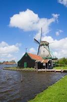 mulino a vento olandese sulle acque del fiume foto