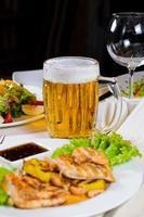 boccale di birra in mezzo a piatti placcati sul tavolo foto