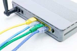 primo piano di cavi di rete collegati al router wifi su bianco foto