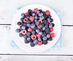bacche ghiacciate sul piatto, il colore di sfondo in legno