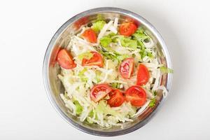 insalata fresca in una piastra di metallo su bianco foto