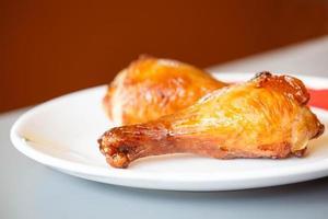 cosce di pollo arrosto sul piatto bianco